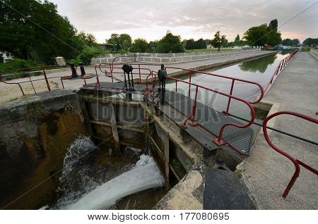 Closed gate of the lock  on the Burgundy channel. The water flows in the foreground.