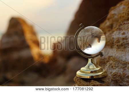 Glass globe on the rock. Yellow stones.