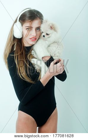 Pretty girl or beautiful woman in earmuffs holding cute pomeranian dog or puppy pet in woollen mittens and using smartphone mobile phone on white background