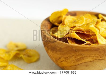 Fried plantain chips in a wooden bowl. Image of homemade healthy snack.