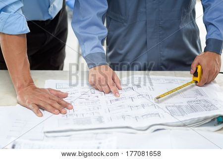 Asian Civil engineer and Asian foreman working on blueprint. Architects workplace - architectural project blueprints ruler calculator and divider compass. Construction concept. Engineering tools