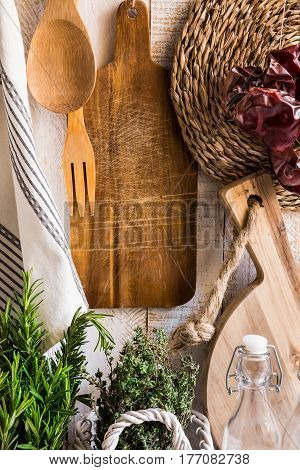 Rustic Provence kitchen interior fresh herbs rosemary thyme wood cutting boards utensils linen towel dried peppers glass bottles on white background daylight