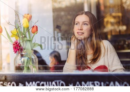 Beautiful smiling young woman sitting in cafe and thoughtfully looking out of the window.