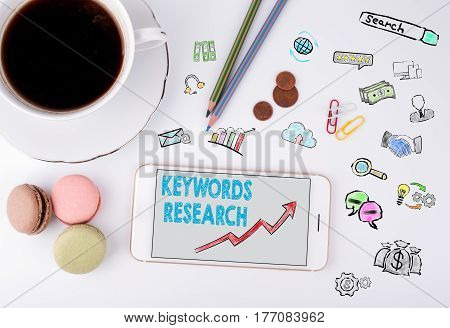 Keywords Research Business Concept. Mobile phone and coffee cup on a white office desk.