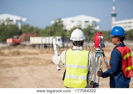 Construction engineer holding drawing and smart tablet with foreman worker checking construction site for new Infrastructure construction project.photo concept for engineering work