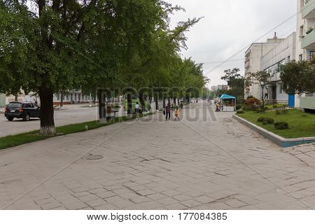 Kaesong, North Korea - July 30, 2014: People walk down the street in Kaesong, North Korea. The city of Kaesong is on the border with South Korea.
