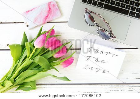 Share the Love message with pink tulips on a white wooden background