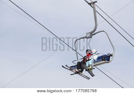 Bukovel Ukraine March 15 2017: Mother and daughter in ski suits and with skis on the ski lift.