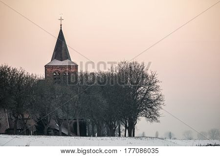 church tower rises above a row of trees in a typical small Dutch village behind the dike during the winter season