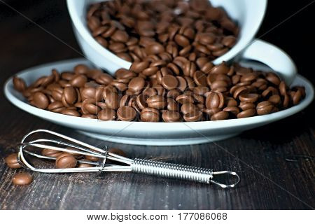 Chocolate beans spilled from a white cup with beater.