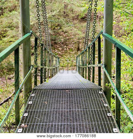Diminishing Perspective Of Metal Suspension Footbridge Over River - Vintage Effect