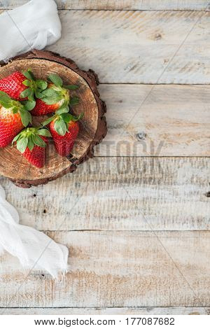 Top view of strawberries over old wooden table background with copy space.