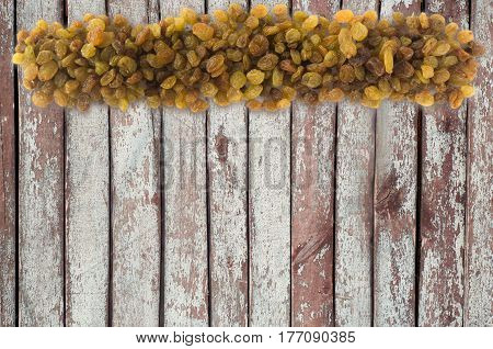 Background made of raisins. Dried fruit with copy space for text. The scattered of a raisins on a wooden background. Top view.