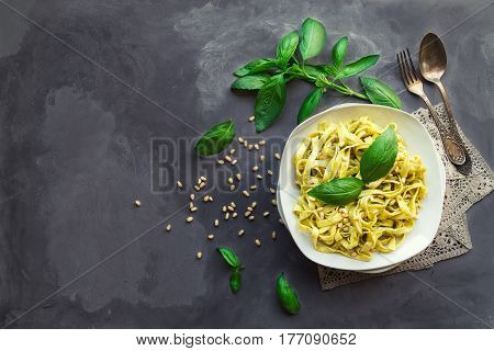 Fettuccine pasta with pesto sauce basil and pine nuts on concrete background. Italian cuisine. Top view. Copy space area.
