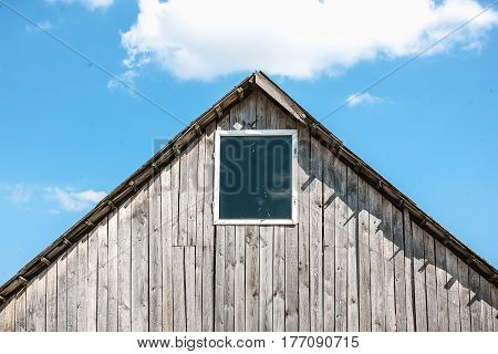Unpainted old wooden shed with window and blue sky