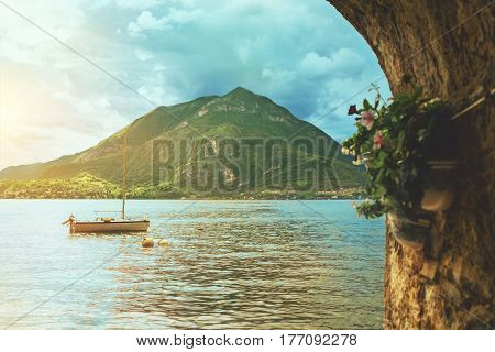 Beautiful colorful panoramic view of waterscape of Como lake coastline with a boat mountain and cloudy sky