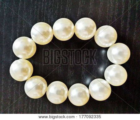 Beads from pearls. Pearl necklace. White pearls on a dark background