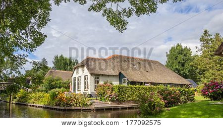Panorama of a white farm house with thatched roof in Giethoorn Netherlands