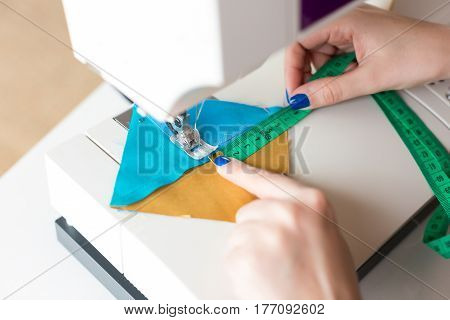 female hands scribbles on the sewing machine geometric color fabric pieces. the process of creating patchwork quilt. the fashion designer's hands at the sewing machine close up. sewing concept.