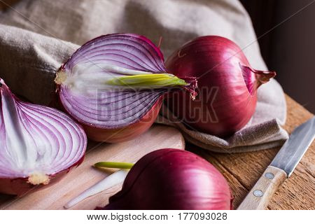 Red or purple onion cut in half green germs wood breadboard linen towel knife kitchen table by window rustic style