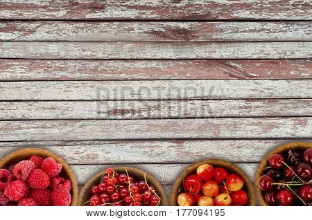 Red berries at border of image with copy space for text. Raspberry strawberry pomegranate currant in a wooden bowls. Top view.