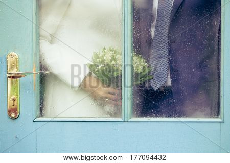 The bride and groom with a bouquet of lilies of the valley standing behind the door with glass hiding from the rainy weather