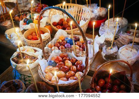 Festive Easter table with Easter food in baskets-eggs cakes candles before the blessing