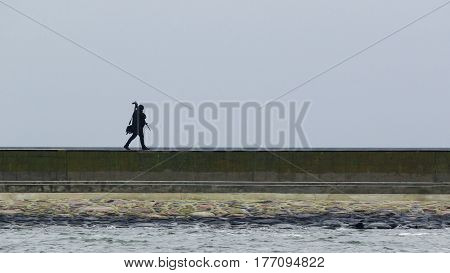 CAMERAMAN ON THE BREAKWATER - Man with tripod goes along shore protection
