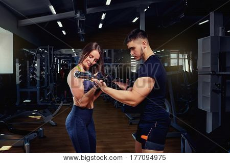 Personal trainer helps a girl lifting weights in the gym.