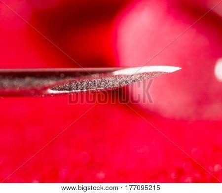 syringe needle on a red background. close