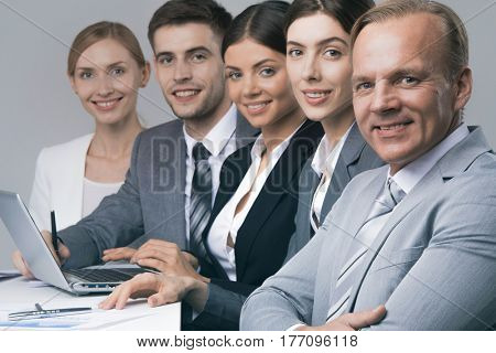 Smiling business people sitting in a row and working at the table with laptop