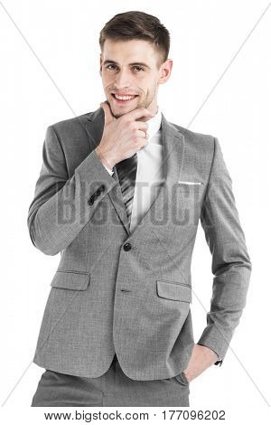 Portrait of handsome smiling young business man holding hand on chin isolated on white background
