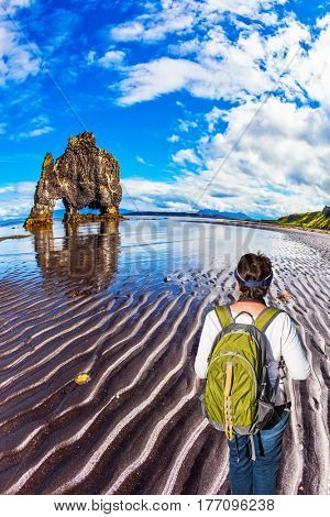 Northern coast of Iceland. Woman with a green backpack admires magic Rock Hvitsercur. Concept of extreme northern tourism