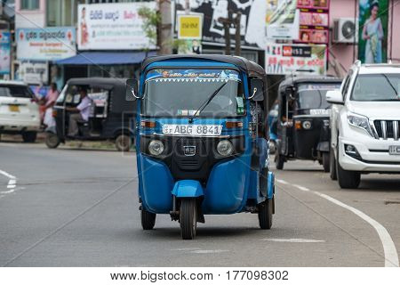 MIRISSA SRI LANKA - January 01 2017: Tuk-tuk moto taxi on the street. Famous thai moto-taxi called tuk-tuk is a landmark of the country and popular transport.