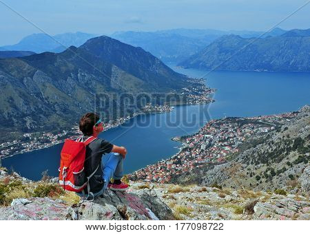 Lonely traveler sitting ot the top. Bay of Kotor Montenegro