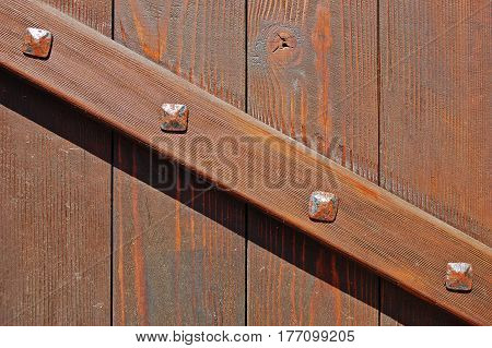 Fragment of old wooden gate with diagonal brace fastened with rusty forged bolts