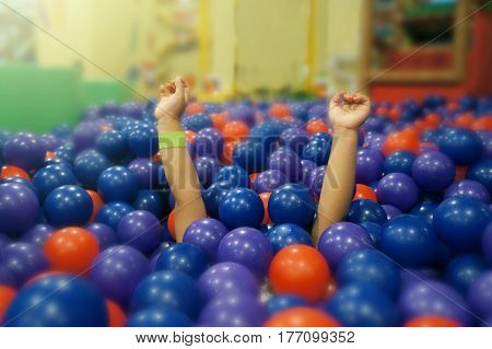 A little girl under plastic balls in ball pit having fun with her arms lifted up.