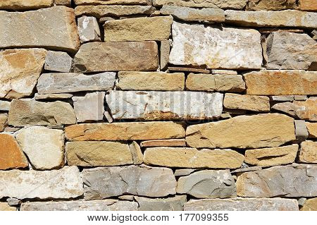 A rough wall made of different colored non-cemented stones