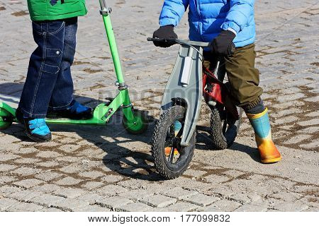 Walks in the fresh air. A child riding scooters on the pavement in the cold season. The second boy stands next to running bikes.