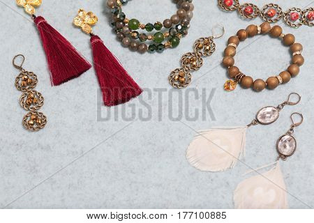 Handmade set of greengoldenbronzeivory and vinous bijouterie with gems tassels cryslals and feathers lying on the gray wool background perspective view with empty place for your text
