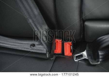 Car seat belt on the black upholstery of the chair with shallow depth of field