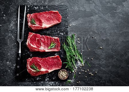 Raw meat beef steak on black background top view