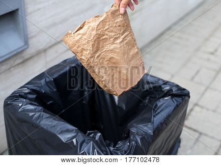 Hand Throwing A Crumpled Paper Bag In The Trash On Street