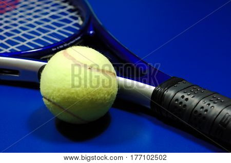 Tennis racket and ball on a blue court surface