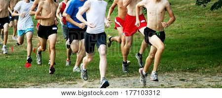 High school boys running on grass in a cross country race