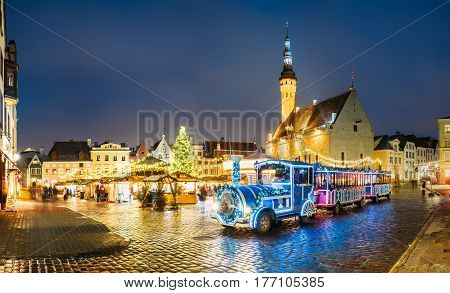 Beautiful Train for sightseeing near Traditional Christmas Market On Town Hall Square - Raekoja Plats In Tallinn, Estonia. Christmas Tree And Trading Houses. Famous Landmark.