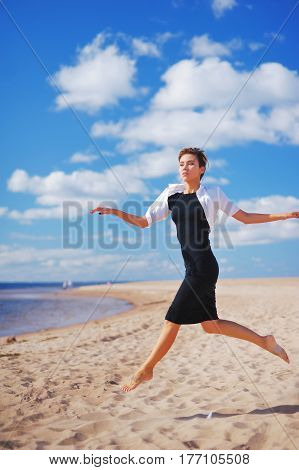 Magnificent portrait of young slim woman in a black dress with a white Bolero, running barefoot on the sand to the sea on the background of blue sky and floating on it white clouds.