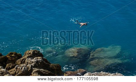 Upper view man swim in transparent tranquil turquoise Mediterranean sea.