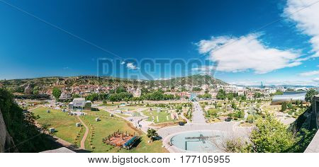 View Of Park Rike In Tbilisi, Georgia. In Background Is Visible Metekhi Church, Narikala Fortress, Old District, Cableway, Sioni Church, Bridge Of Peace, Mount Mtatsminda, Theatre Of Music And Drama