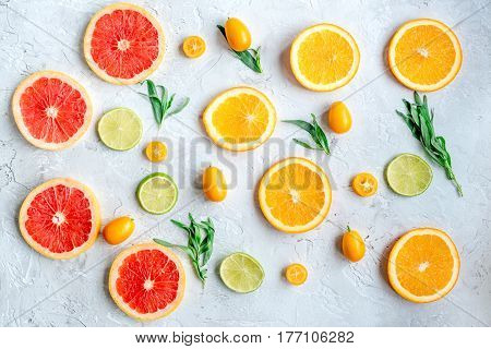 fruit pattern with cut blood orange and lime on gray stone table background top view